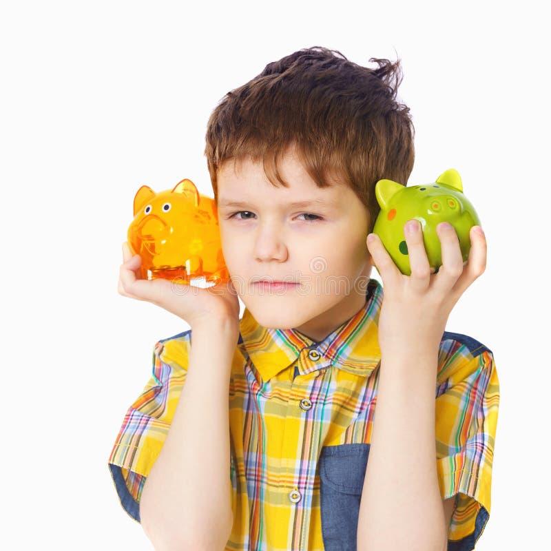 Bambino che tiene un porcellino salvadanaio, colpo dello studio su un fondo leggero fotografia stock libera da diritti
