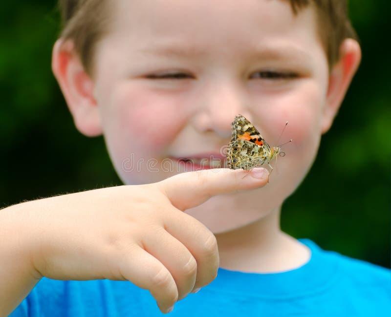 Bambino che tiene una farfalla fotografie stock