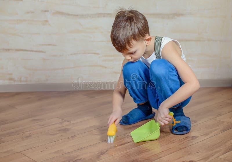 Bambino che usando la scopa e paletta per la spazzatura del giocattolo immagini stock