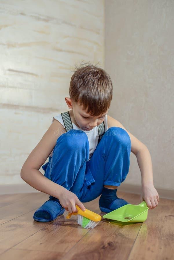 Bambino che usando la scopa e paletta per la spazzatura del giocattolo fotografie stock