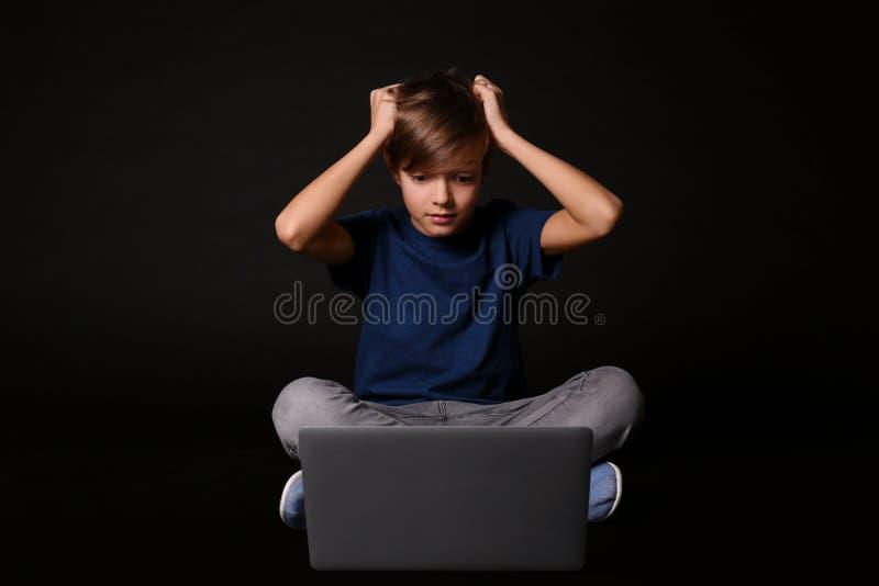 Bambino colpito con il computer portatile sul nero Il pericolo di Internet fotografie stock libere da diritti