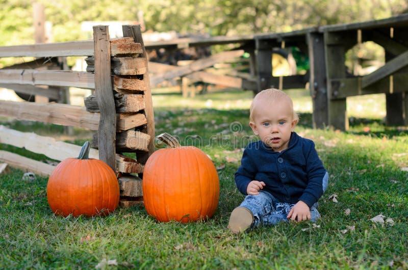 Bambino con due zucche mature Zucche di raccolto nella toppa della zucca fotografia stock libera da diritti