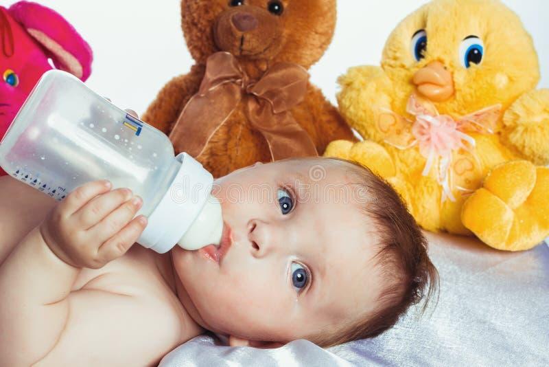 Bambino con gli occhi azzurri che beve da una bottiglia immagine stock