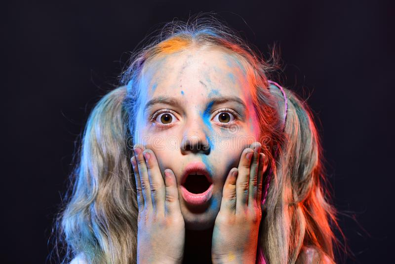 Bambino con i colori delle code di cavallo La scolara ha punti della pittura sul fronte fotografia stock