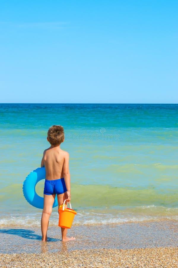 Bambino con i giocattoli, esaminanti il mare fotografie stock