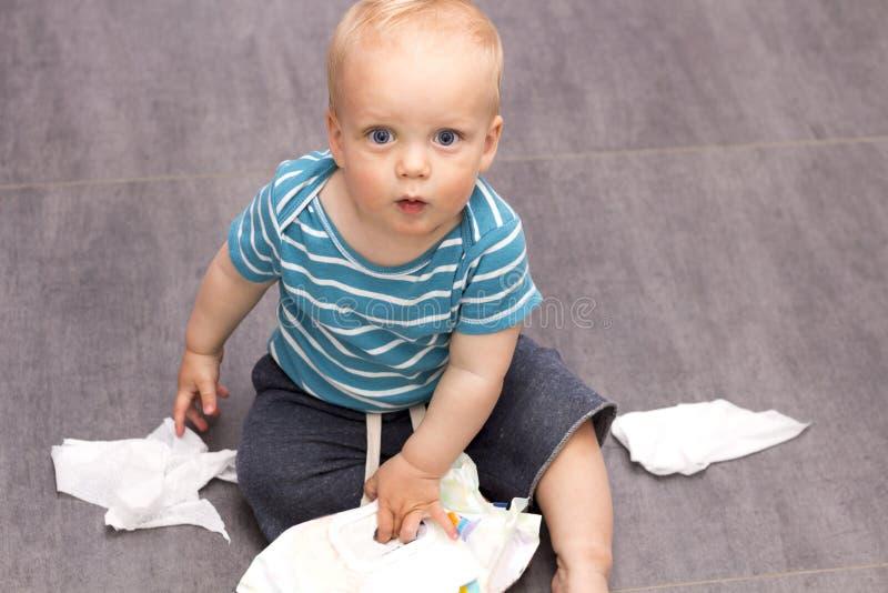 Bambino con i occhi spalancati sveglio che si siede con le strofinate sparse sul pavimento immagine stock libera da diritti