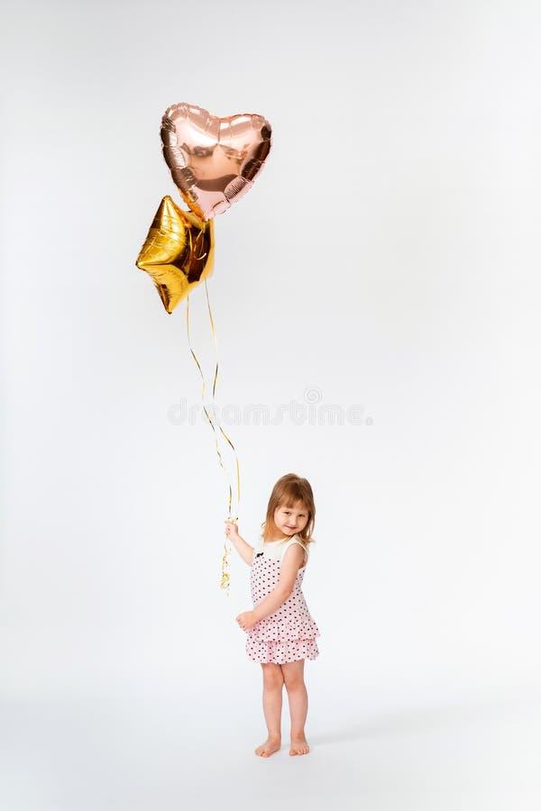 Bambino con i palloni a forma di del cuore fotografia stock