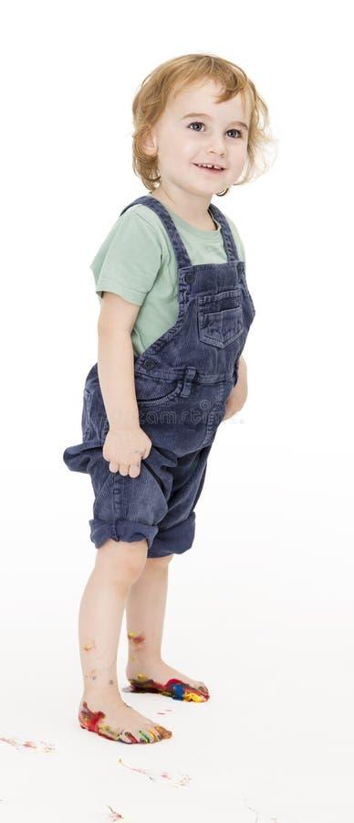Bambino con i piedi dipinti che tengono i pantaloni fotografia stock libera da diritti