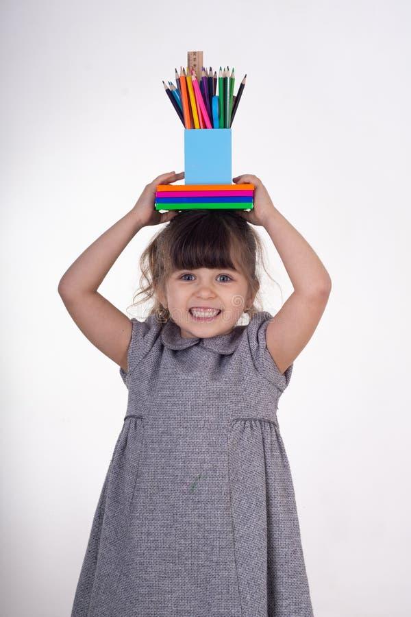 Bambino con i rifornimenti della pittura e di tiraggio Scherza felice di ritornare a scuola Bambini creativi sopra fondo bianco immagine stock libera da diritti