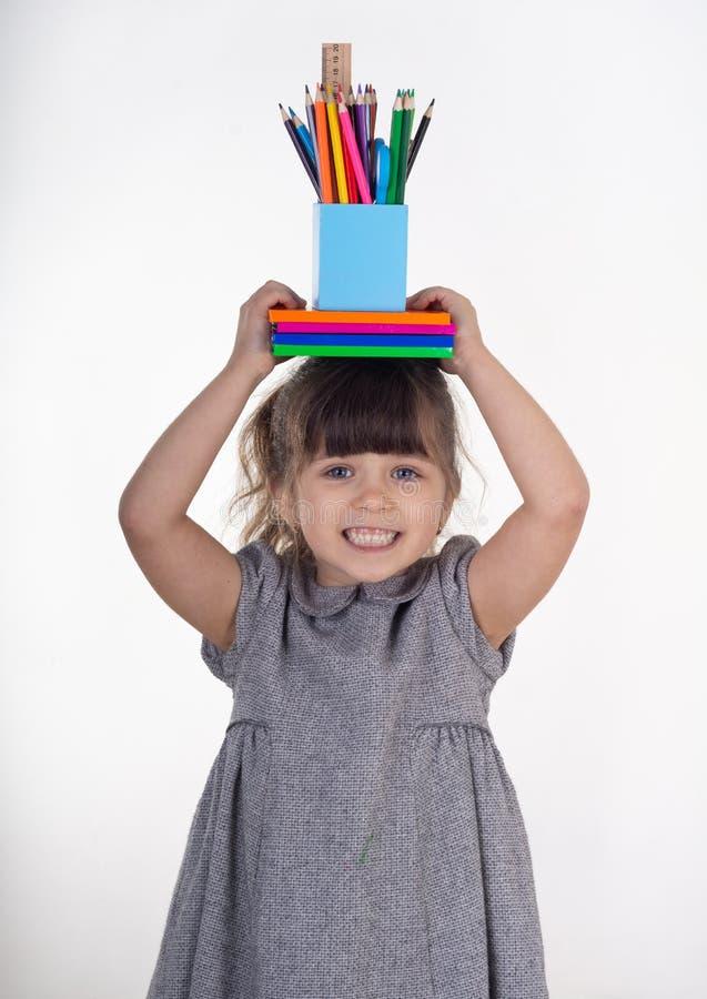 Bambino con i rifornimenti di scuola della pittura e di tiraggio Scherza felice di ritornare a scuola fotografia stock libera da diritti