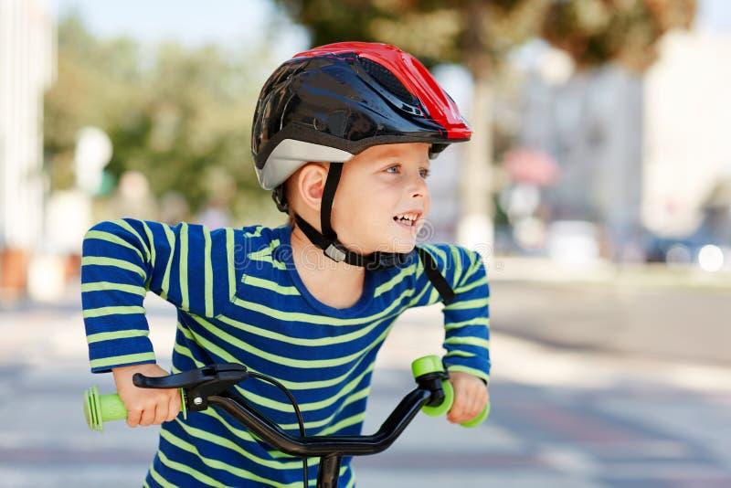 Bambino con i sorrisi del casco e della bici immagine stock libera da diritti