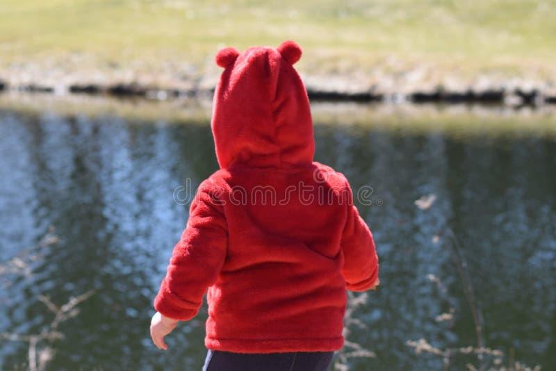 Bambino con il cappotto rosso che si siede davanti allo stagno immagine stock