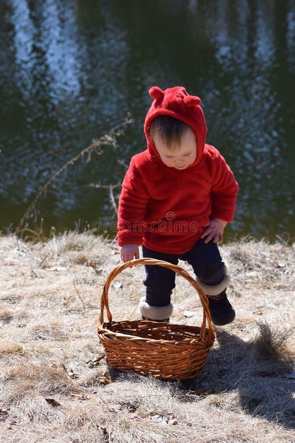 Bambino con il cappotto rosso che si siede davanti allo stagno con il canestro immagine stock