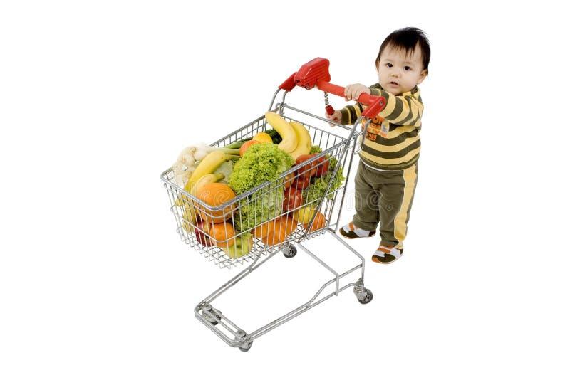 Bambino con il carrello di acquisto immagine stock libera da diritti