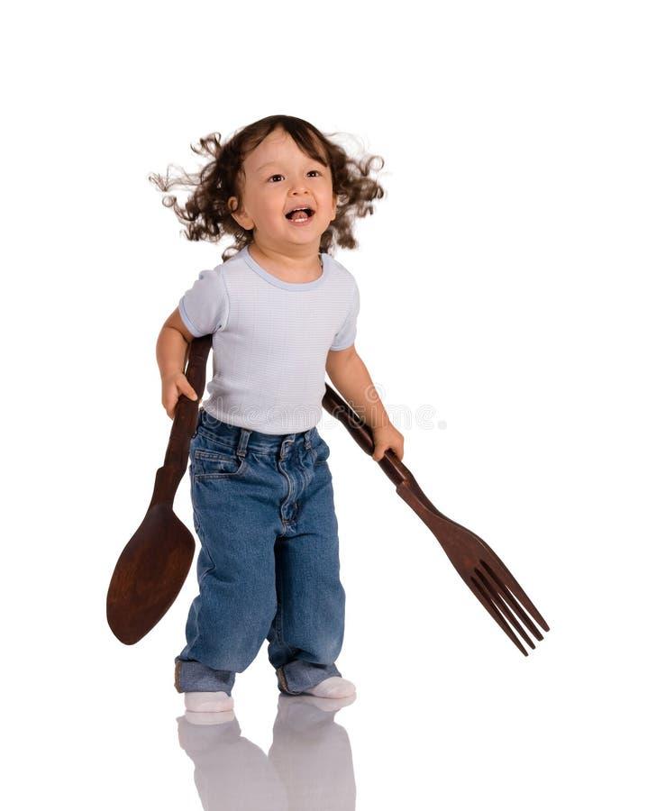 Bambino con il cucchiaio e la forchetta immagini stock libere da diritti