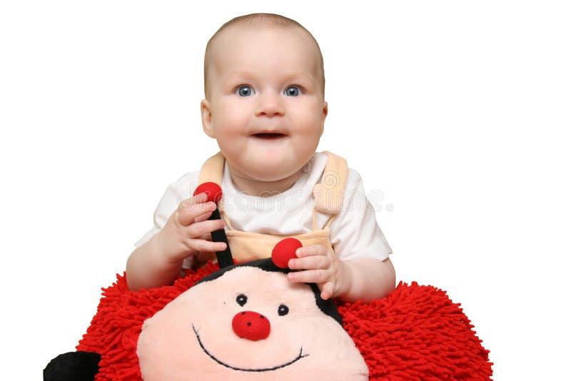 Bambino con il cuscino del ladybug immagine stock