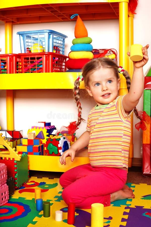 Bambino con il puzzle e blocco di legno nella stanza del gioco. fotografia stock