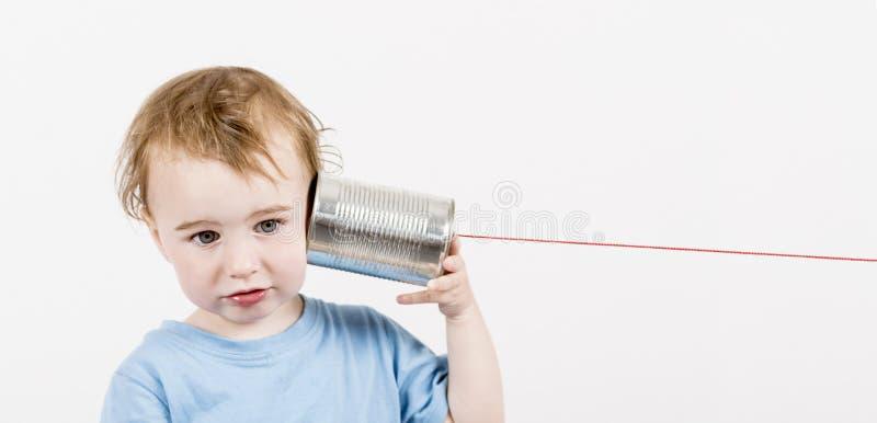 Bambino con il telefono del barattolo di latta fotografia stock libera da diritti