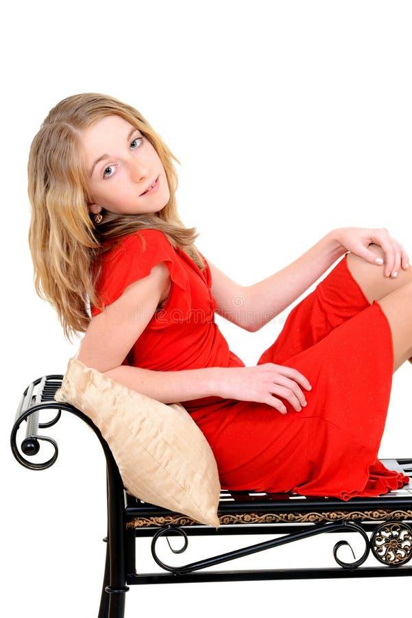 Bambino con il vestito rosso sul banco fotografie stock libere da diritti