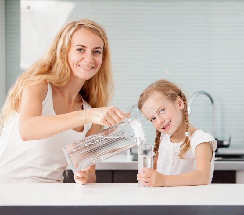 Bambino con l'acqua potabile della madre fotografie stock