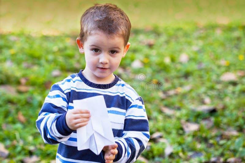 Bambino con l'aeroplano di carta immagini stock libere da diritti