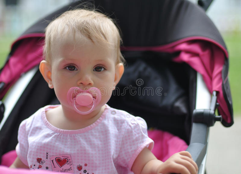 Bambino con l'ugello che si siede in carrozzina immagini stock libere da diritti