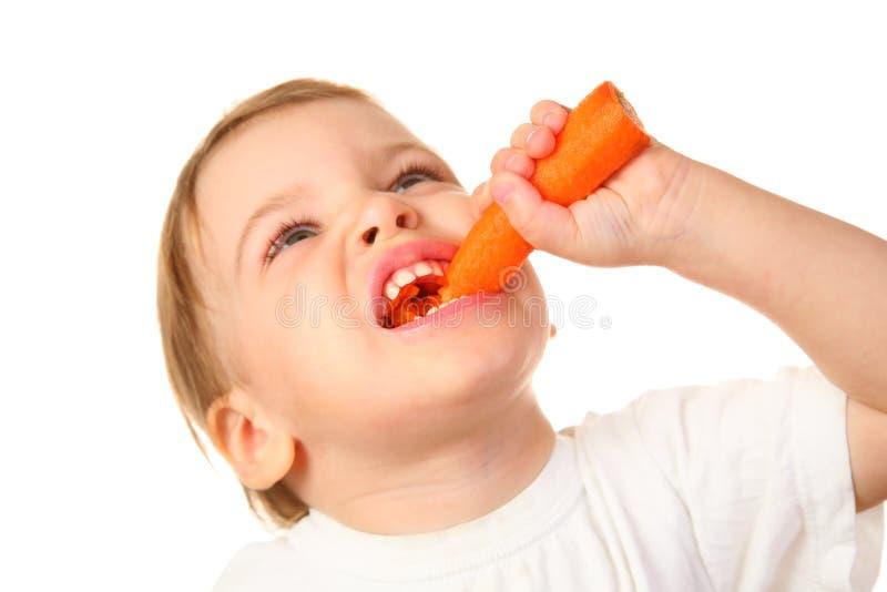 Bambino con la carota fotografia stock