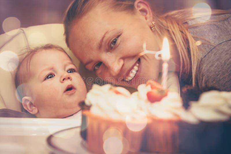 Bambino con la madre che esamina torta di compleanno con la candela durante il primo compleanno di celebrazione fotografia stock libera da diritti