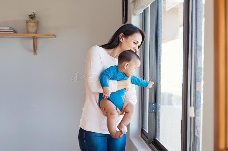 Bambino con la madre che guarda fuori immagine stock libera da diritti