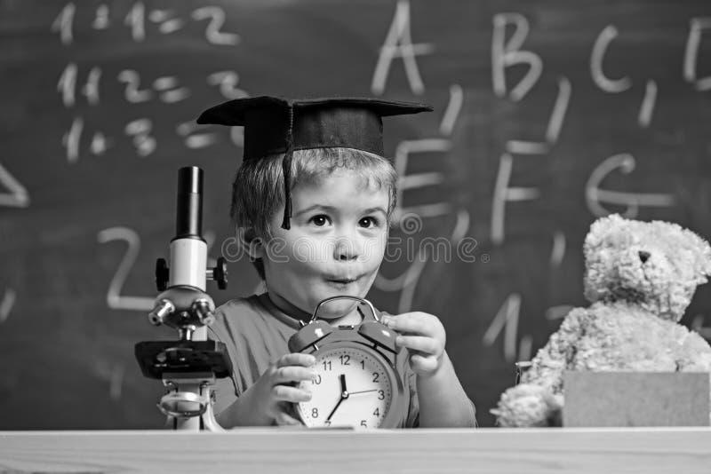 Bambino con la sveglia sulla tavola Ritratto del ragazzo sveglio che impara nell'aula Ragazzo del bambino in cappuccio accademico immagine stock