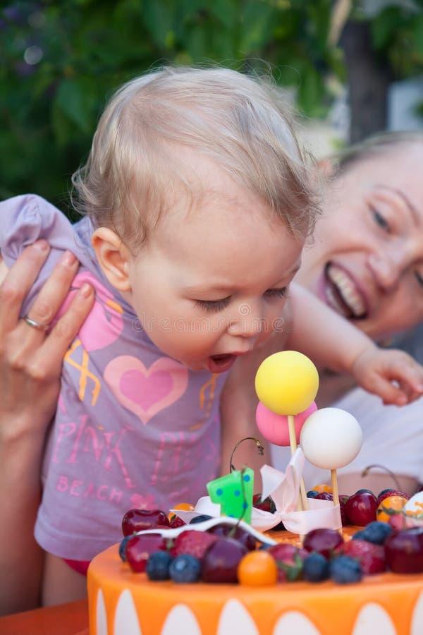 Bambino con la torta di compleanno durante la celebrazione della sua prima festa di compleanno fotografia stock