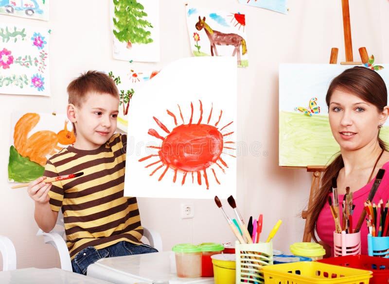 Bambino con la vernice di tiraggio dell'insegnante nella stanza del gioco. fotografia stock