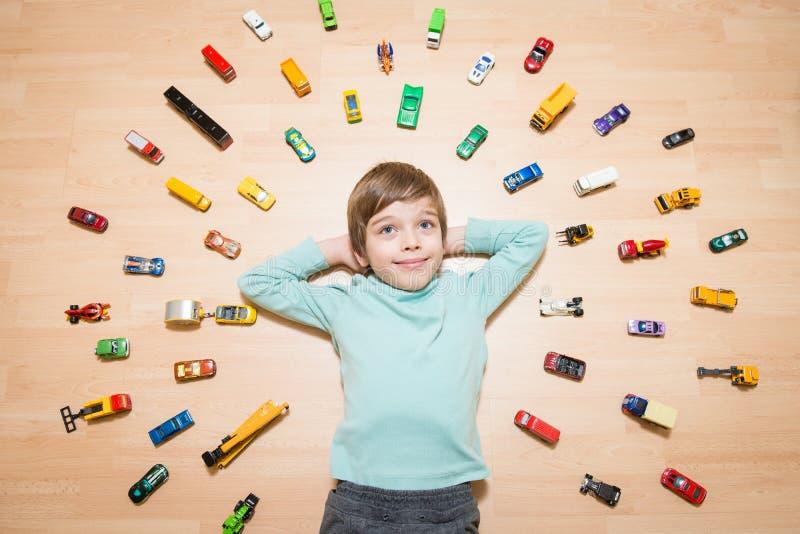 Bambino con le automobili del giocattolo intorno lui immagine stock libera da diritti