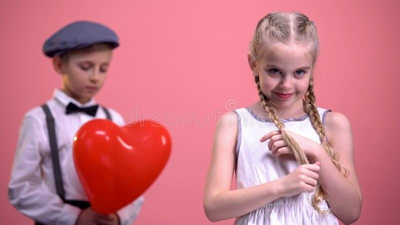 Bambino con le trecce che sorride alla macchina fotografica con il ragazzo timido nel fondo, primo amore fotografie stock