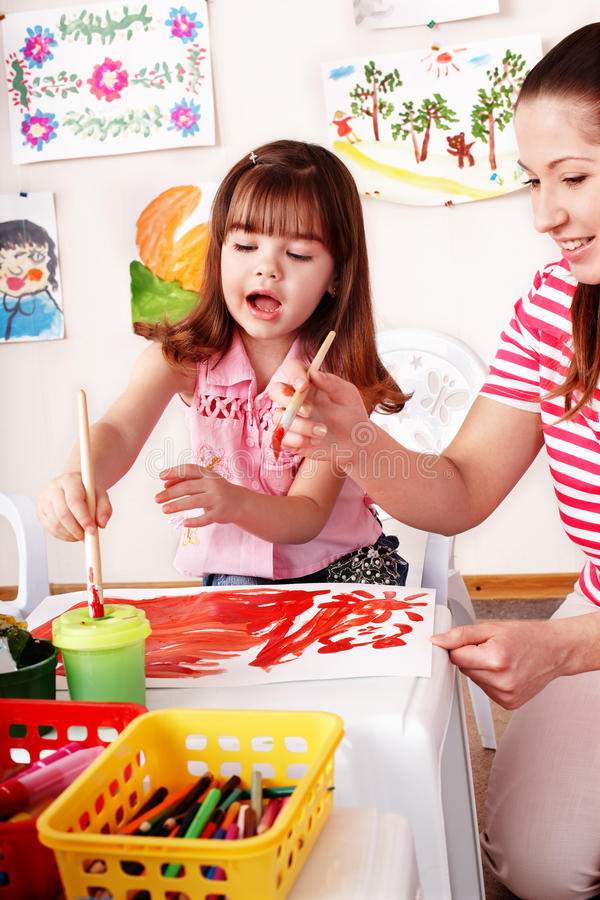 Bambino con le vernici di tiraggio dell'insegnante nella stanza del gioco. fotografie stock