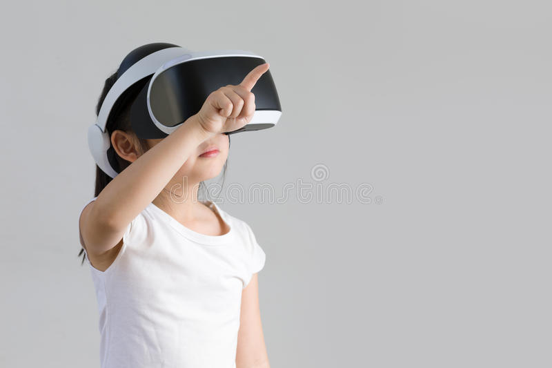 Bambino con realtà virtuale, VR, colpo dello studio della cuffia avricolare isolato su fondo bianco Bambino che esplora il mondo  immagine stock