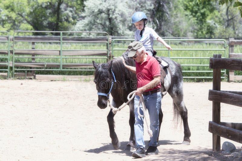 Bambino con un casco di sicurezza Goes su Pony Ride ad un'azienda agricola locale con il suo cavallo che è di prima generazione p immagini stock