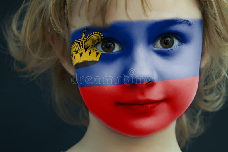 Bambino con una bandiera dipinta del Liechtenstein immagine stock libera da diritti