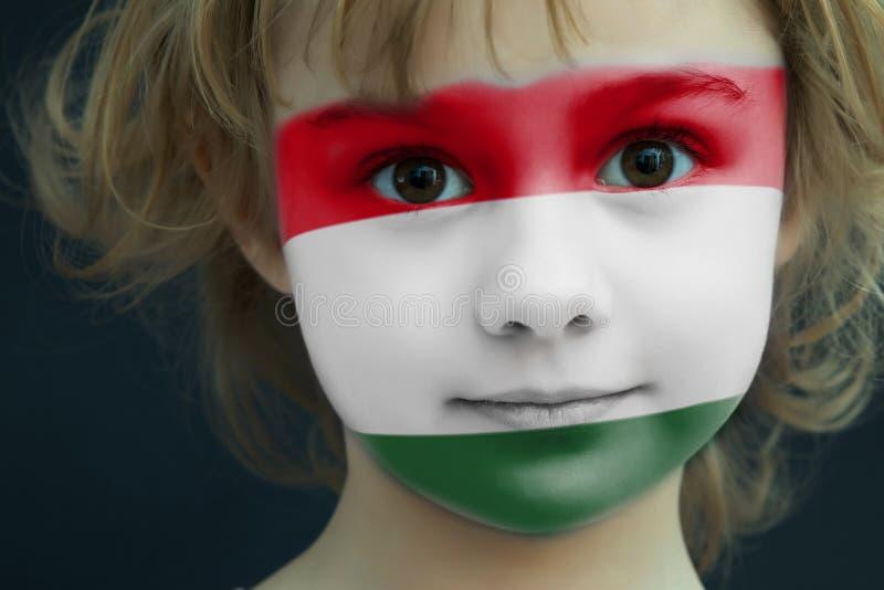 Bambino con una bandiera dipinta dell'Ungheria immagine stock libera da diritti