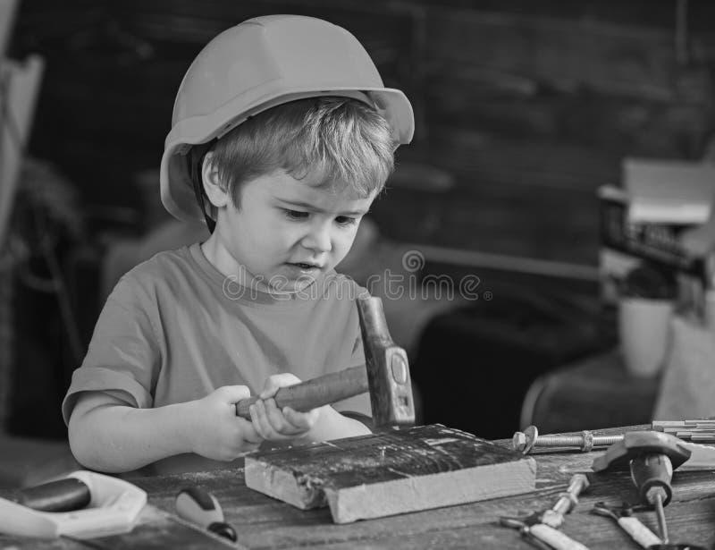 Bambino concentrato che lavora con il martello Ragazzino che guadagna le nuove abilità Bambino in età prescolare che impara marte fotografia stock libera da diritti