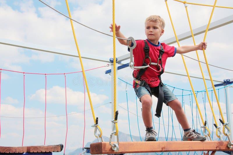 Bambino coraggioso dei capelli biondi che gioca corso della corda all'aperto immagini stock libere da diritti