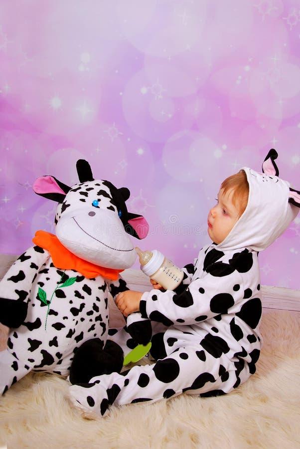 Bambino in costume della mucca che alimenta una mascotte della mucca fotografia stock libera da diritti