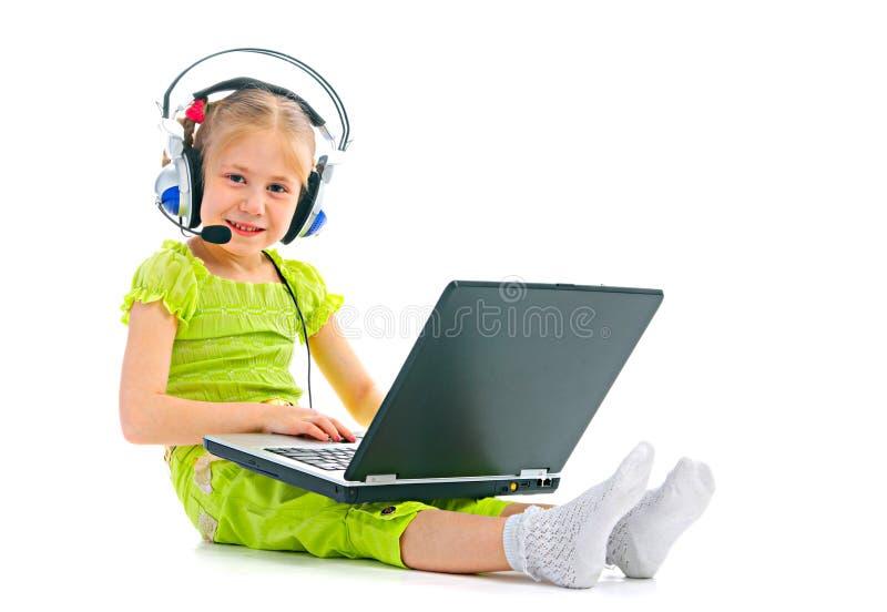 Bambino in cuffie con il computer portatile immagine stock