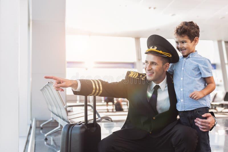 Bambino d'abbraccio dell'aviatore allegro del papà fotografia stock
