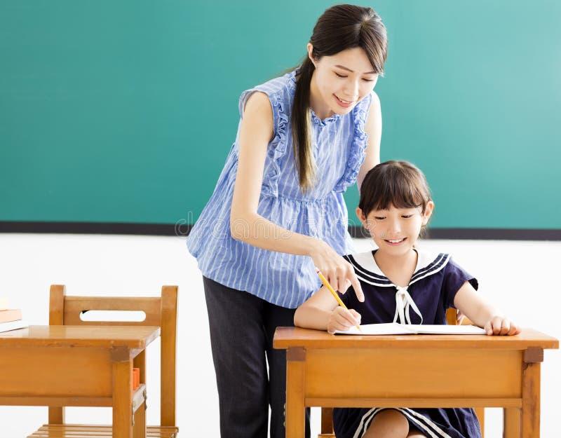 Bambino d'aiuto del giovane insegnante con la lezione di scrittura fotografia stock libera da diritti