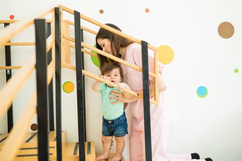 Bambino d'aiuto del terapista scalare le scale fotografie stock libere da diritti