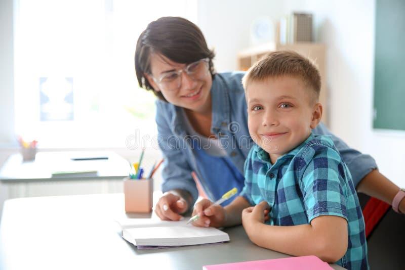 Bambino d'aiuto dell'insegnante femminile con l'assegnazione alla scuola fotografia stock