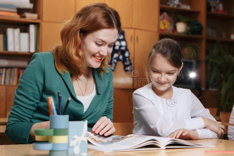 Bambino d'aiuto della madre dopo la scuola bambino in età prescolare che fa compito con aiuto dell'istitutore concetto d'istruzio immagini stock