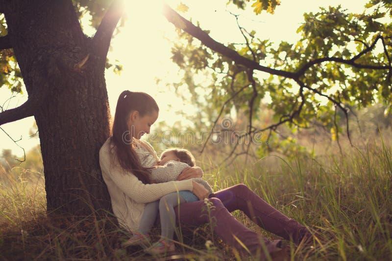 Bambino d'alimentazione della madre all'aperto fotografia stock libera da diritti