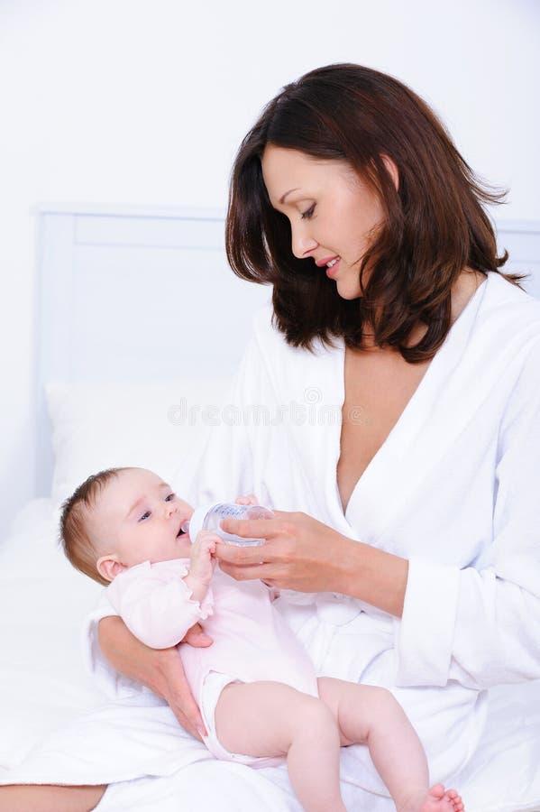 Bambino d'alimentazione della madre con la bottiglia fotografie stock libere da diritti